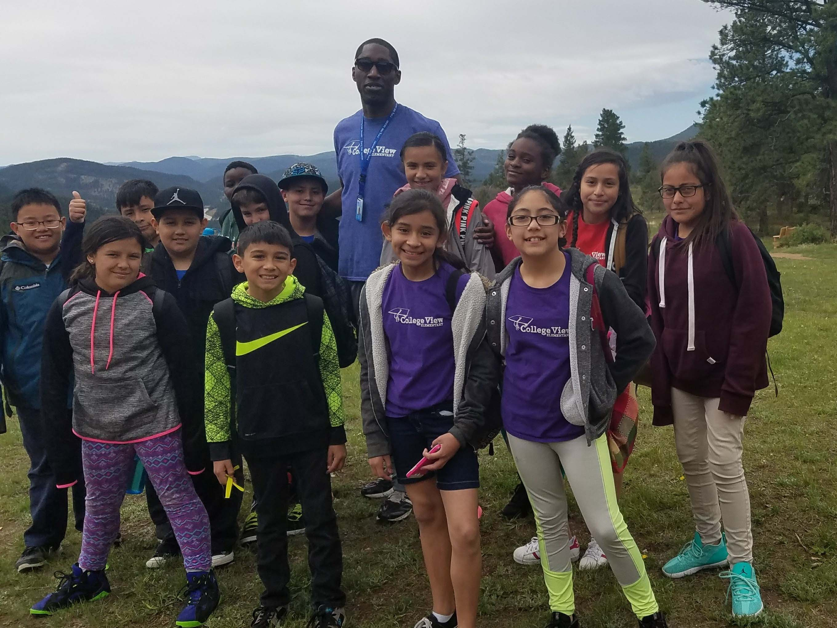 Group of middle school children on top of the mountain with a teacher