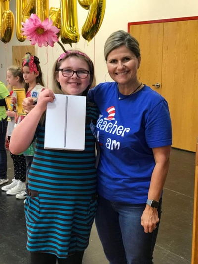 Ms. McEntire with a student who won the Great Reading Games standing together smiling.
