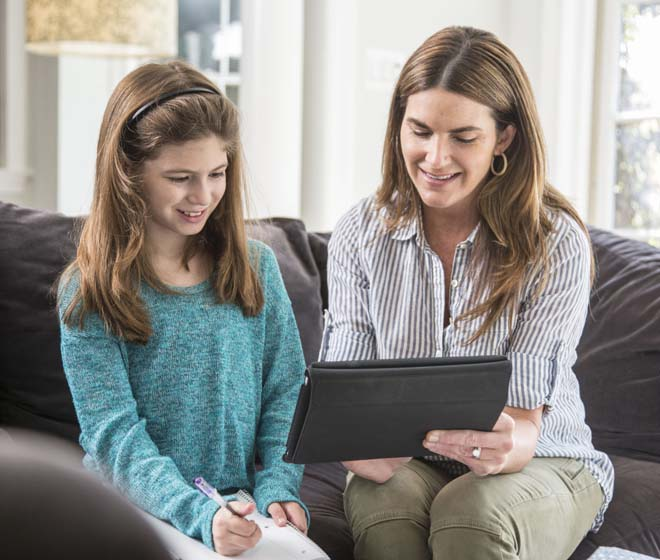 Mother and Daughter sitting on the couch, looking at the tablet