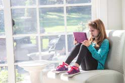Young girl sitting alone at home on a sofa with tablet, reading