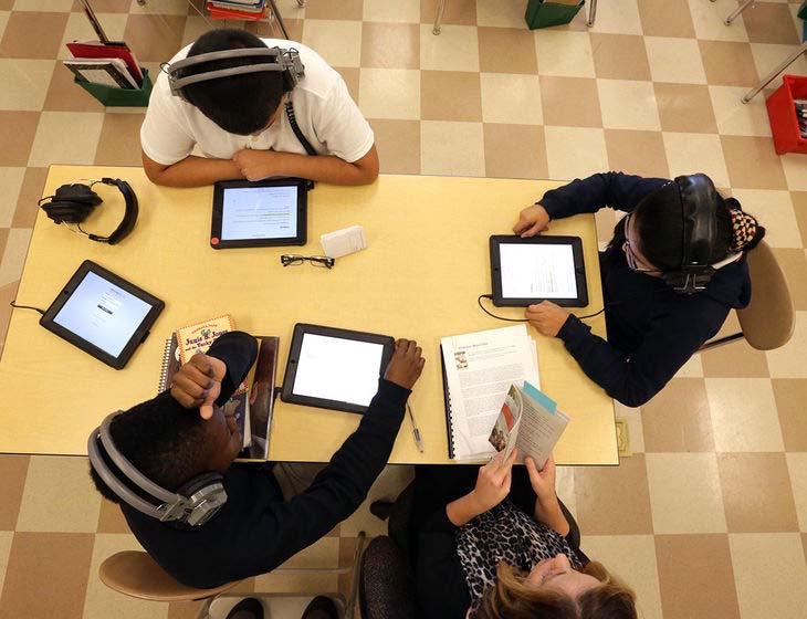 Students sitting around a table reading their tablets