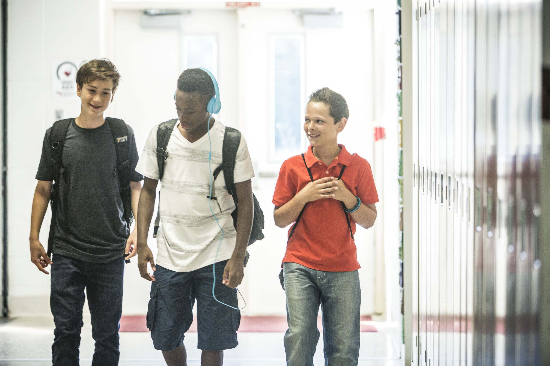three teen boys walking in school hallway
