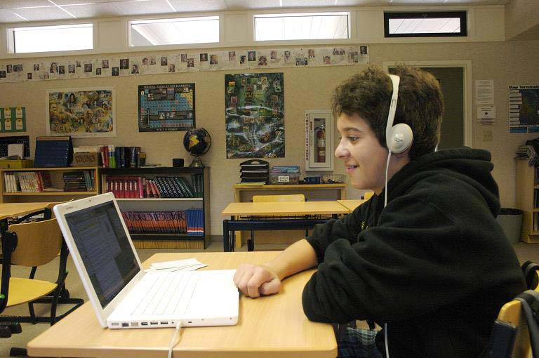 Male student with headphones enjoying an audiobook.