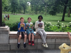 3 kids with books in Central Park