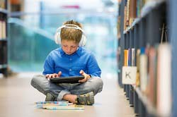 Student Reading Audiobooks in Library