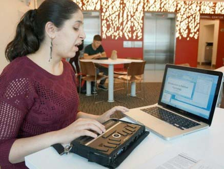 Student with braille note-taker and open laptop