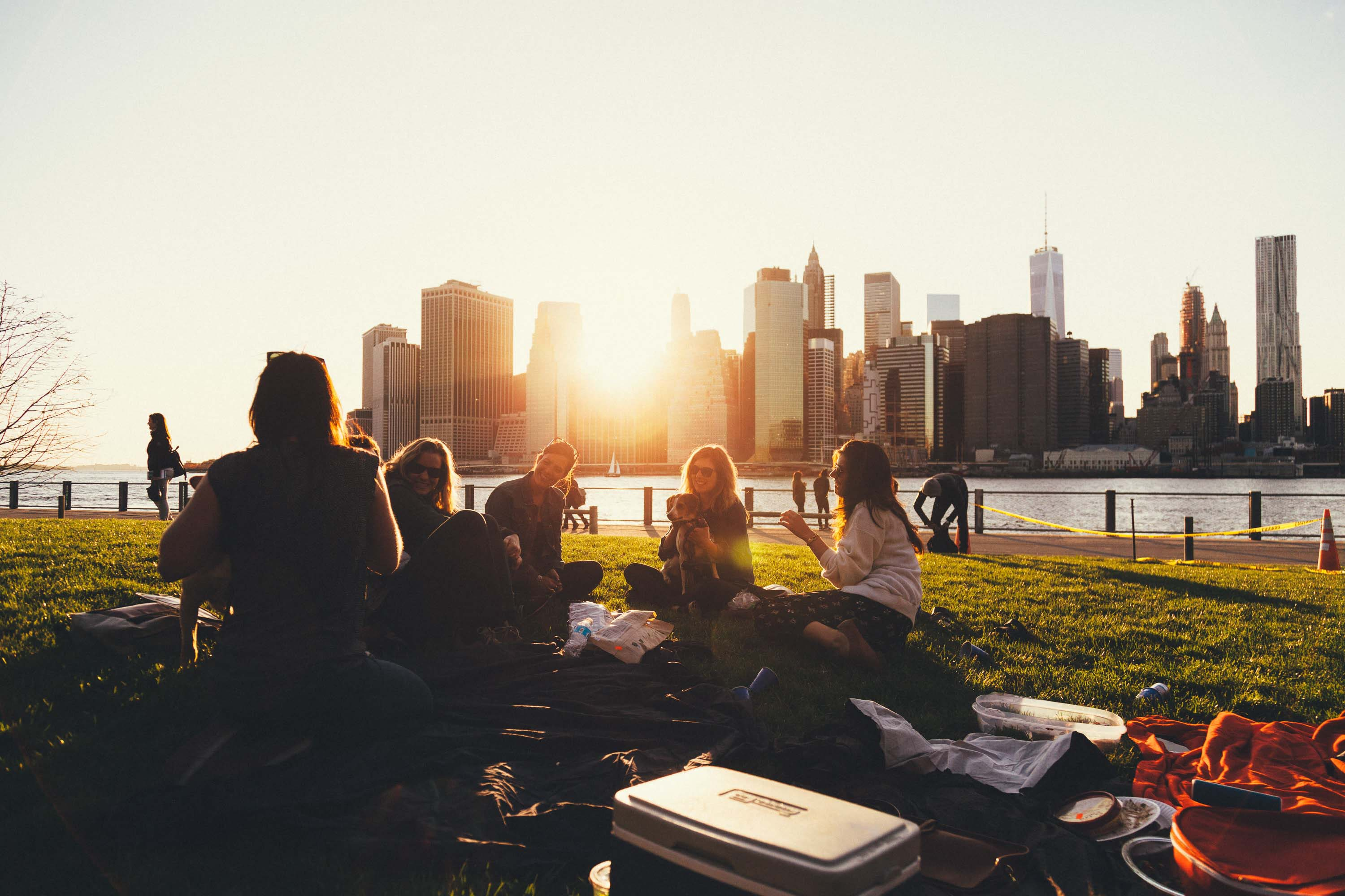A group of 5 female friends are having a picnic on a grassy lawn. Two of the women have their dogs with them. In the background is a river and a city skyline, with the sun setting behind the buildings.