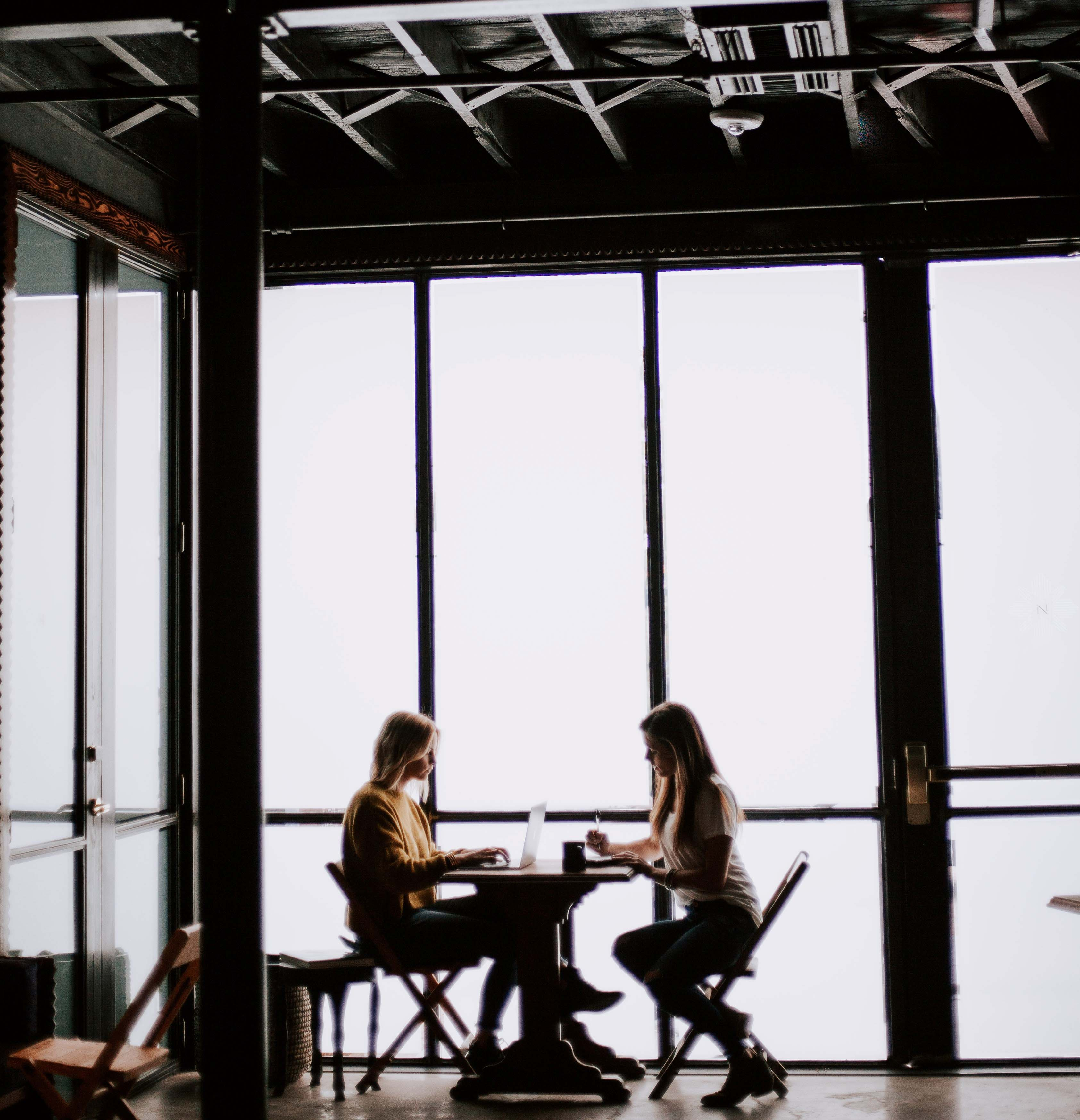 Two women sit in conversation at a table in front of a large window.