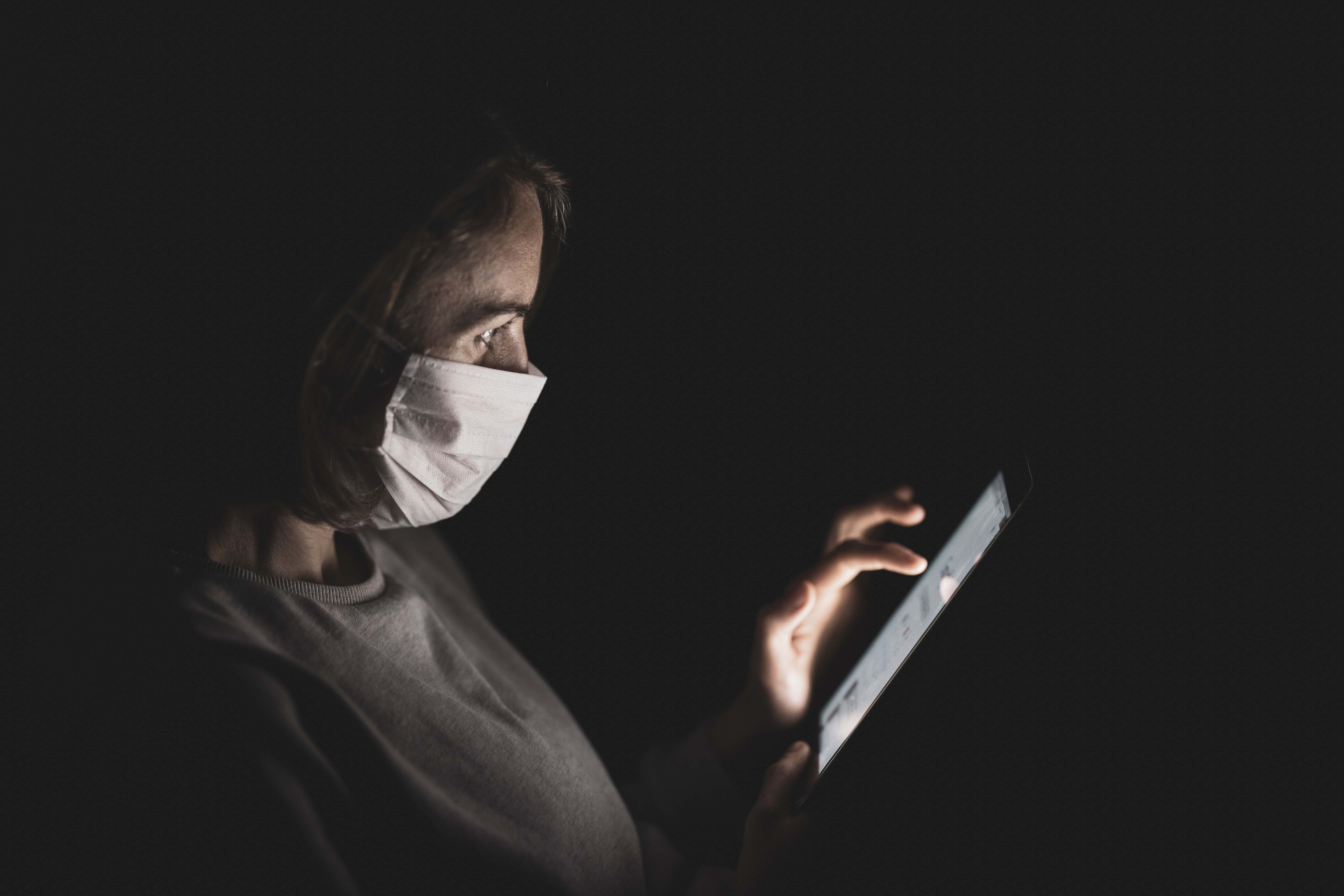 Woman wearing a face mask for protection from coronavirus. She is sitting in the dark, illuminated from the light of a tablet that she is working on.