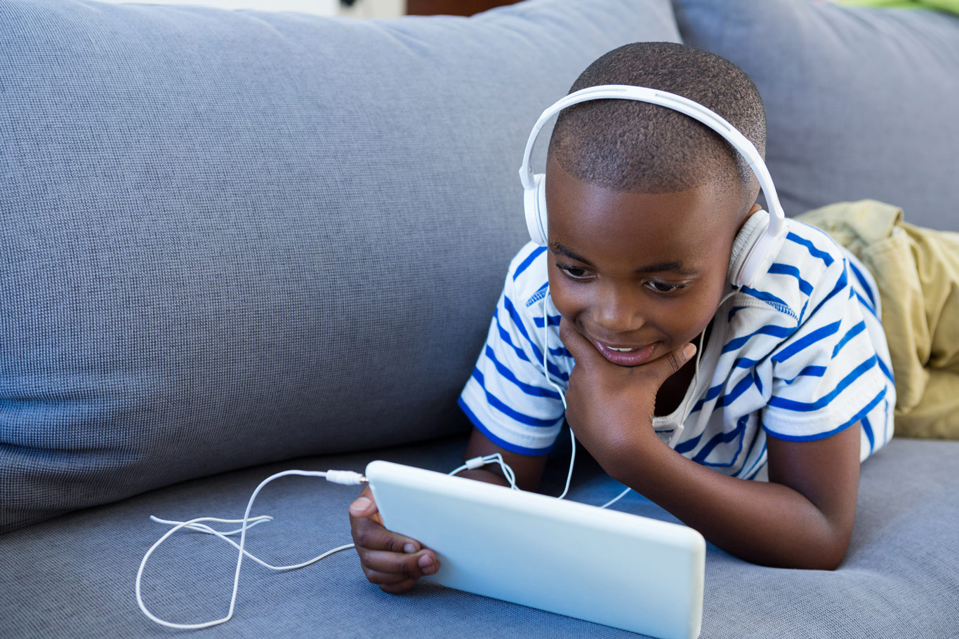 young boy listening to audio book on ipad
