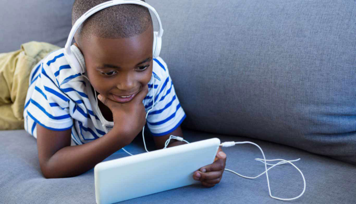 school age boy reading audio book on a tablet